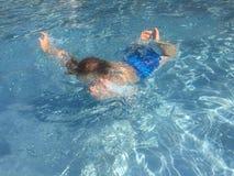 Bambino che si tuffa lo stagno di acqua blu fotografie stock