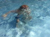 Bambino che si tuffa lo stagno di acqua blu fotografie stock libere da diritti