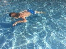 Bambino che si tuffa lo stagno di acqua blu immagini stock