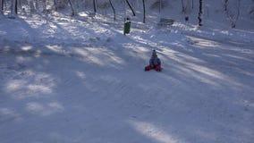 Bambino che Sledding nella neve, bambina che gioca nell'inverno, bambino Sledging in parco 4K archivi video