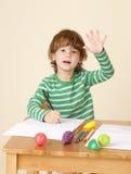 Bambino che solleva mano a scuola Fotografia Stock