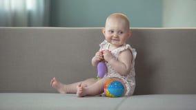 Bambino che sorride e che gioca con i giocattoli sul sofà, infante che gode della comodità in pannolini archivi video