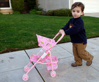Bambino che spinge carrozzina fotografia stock