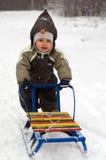 Bambino che spinge slitta Fotografia Stock