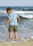 Bambino che sta alla spiaggia in acqua Fotografia Stock