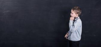 Bambino che sta davanti alla lavagna nera Fotografia Stock