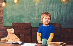 Bambino che sta dietro lo scrittorio di legno Tavola di legno scura con i quaderni, l'orsacchiotto, la tazza ed il mucchio dei li immagine stock libera da diritti