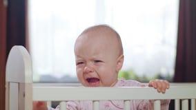 Bambino che sta in una greppia a casa gridare stock footage