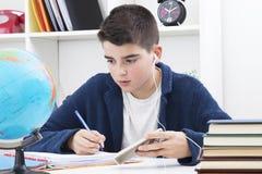 Bambino che studia e che scrive fotografia stock