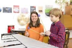 Bambino che studia lo strumento di percussione Fotografia Stock Libera da Diritti
