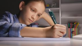 Bambino che studia nella notte, scrittura del bambino nello studente scuro Learning Evening Schoolgirl immagine stock