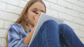 Bambino che studia sulla compressa, ragazza che scrive per la classe di scuola, imparante facendo compito stock footage