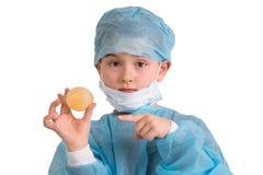 Bambino che tiene e che mostra al suo uovo rimbalzante progetto della scuola elementare Fotografia Stock