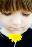 Bambino che tiene un fiore giallo selvaggio fragile Immagini Stock Libere da Diritti