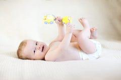 Bambino che tiene un giocattolo e che si trova sulla coperta bianca Fotografia Stock Libera da Diritti
