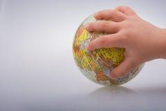 Bambino che tiene un globo in sua mano Immagine Stock
