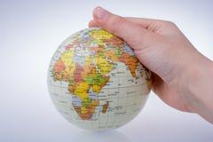 Bambino che tiene un globo in sua mano Fotografie Stock Libere da Diritti