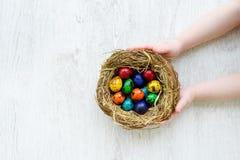 Bambino che tiene un nido con le uova di Pasqua colorate a casa sul giorno di Pasqua Immagine Stock Libera da Diritti