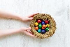 Bambino che tiene un nido con le uova di Pasqua colorate a casa sul giorno di Pasqua Immagine Stock