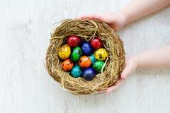 Bambino che tiene un nido con le uova di Pasqua colorate a casa sul giorno di Pasqua Fotografie Stock Libere da Diritti