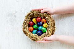 Bambino che tiene un nido con le uova di Pasqua colorate a casa sul giorno di Pasqua Fotografie Stock