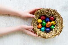Bambino che tiene un nido con le uova di Pasqua colorate a casa sul giorno di Pasqua Immagini Stock Libere da Diritti