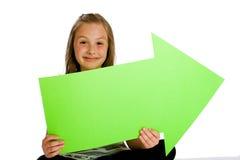 Bambino che tiene un segno verde in bianco della freccia. Fotografia Stock