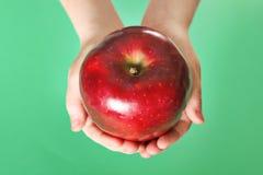 Bambino che tiene una mela rossa su priorità bassa verde fotografia stock