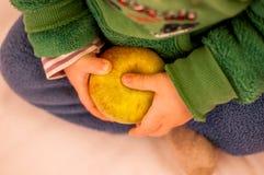 Bambino che tiene una mela in una mano Immagini Stock
