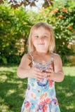 Bambino che tiene vetro di acqua potabile all'aperto fotografia stock libera da diritti