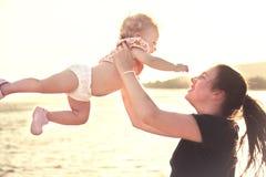 Bambino che tira la sua mano verso la madre mentre giocando alla spiaggia Bambino di cattura della giovane madre felice dopo il l immagini stock libere da diritti