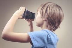 Bambino che usando i nuovi vetri del cartone di VR Immagine Stock Libera da Diritti