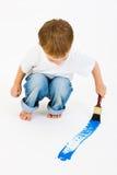 Bambino che vernicia blu con una grande spazzola Fotografia Stock