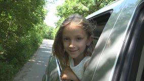 Bambino che viaggia in macchina, fronte del bambino che guarda fuori la finestra, natura piena d'ammirazione della ragazza immagine stock