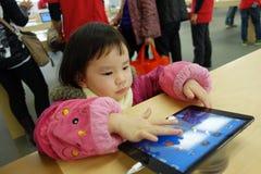 Bambino cinese che gioca ipad nella memoria della mela Fotografie Stock