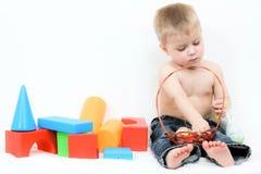 Bambino, circondato dai giocattoli Fotografie Stock Libere da Diritti