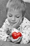 Bambino con cuore rosso. Concetto di giorno dei biglietti di S. Valentino Fotografie Stock Libere da Diritti
