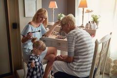 Bambino con divertiresi della nonna e della mamma immagini stock