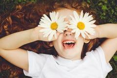 Bambino con gli occhi della margherita, su erba verde in un parco di estate Immagine Stock Libera da Diritti