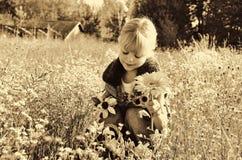 Bambino con i fiori nella seppia Fotografia Stock