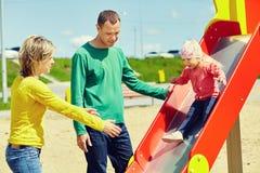 Bambino con i genitori ad un campo da giuoco fotografia stock libera da diritti