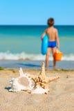 Bambino con i giocattoli, esaminanti il mare Fotografia Stock