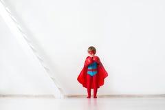 Bambino con i guantoni da pugile e un mantello rosso immagini stock