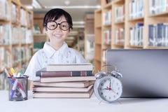 Bambino con i libri di scienza nella biblioteca Immagine Stock