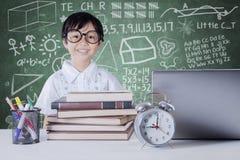 Bambino con i libri ed il taccuino nella classe Fotografia Stock