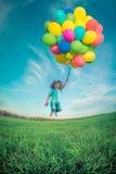 Bambino con i palloni del giocattolo nel giacimento di primavera Fotografie Stock Libere da Diritti