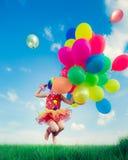 Bambino con i palloni del giocattolo nel giacimento di primavera Immagine Stock Libera da Diritti