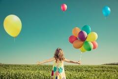 Bambino con i palloni del giocattolo nel giacimento di primavera Fotografia Stock Libera da Diritti