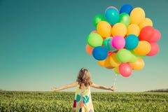 Bambino con i palloni del giocattolo nel giacimento di primavera Fotografia Stock