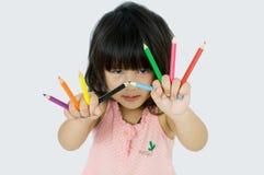 Bambino con i pincils di colore a disposizione Immagine Stock